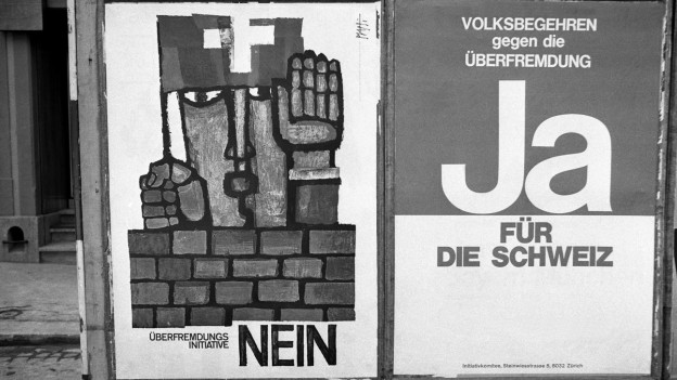 Zwei Plakate (eines für, das andere gegen die Schwarzenbach-Initiative) aus dem Jahr 1970 hängen nebeneinander in Zürich auf der Strasse.