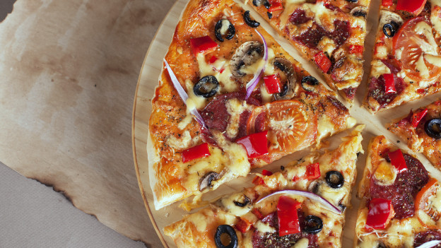 Eine reich belegte und in Stücke zerschnittene Pizza