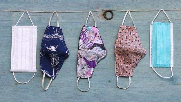 Masken aus Stoff und eine Wegwerfmaske hängen an einer Leine