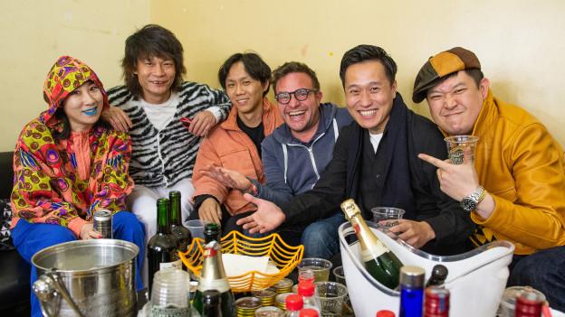 Pascal Nufer sitzt zwischen lachenden Mitgliedern einer Rockband.