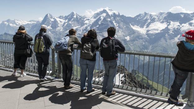 Einige Touristen mit Rucksack schauen vom Schilthorn Richtung Eiger, Mönch und Jungfrau.