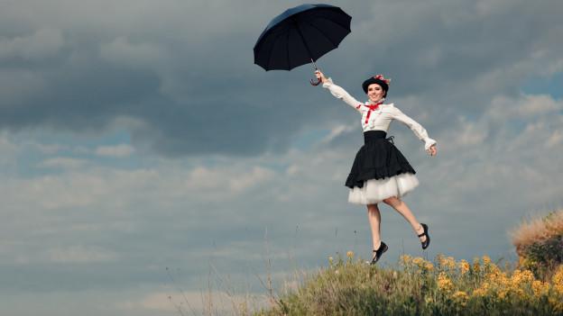 Mary Poppins fliegt - mit ihrem Regenschirm in der Hand - durch die Luft