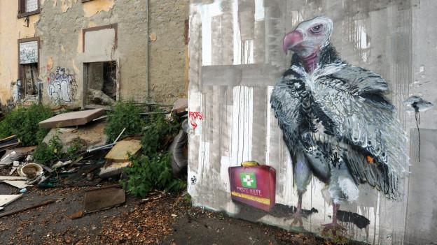 Eine Wand mit einem Graffiti auf einem alten Industriegelände.