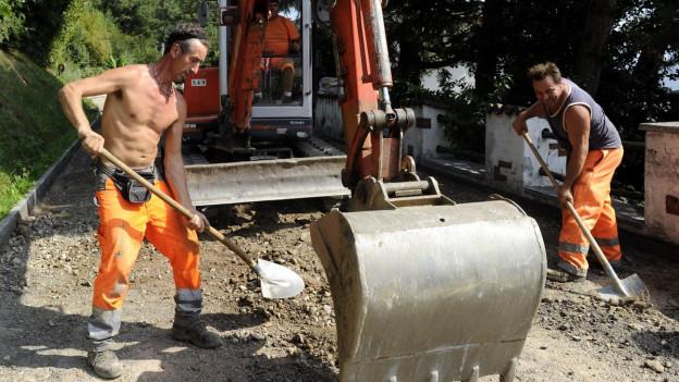 Zwei Strassenbauer verrichten ihre Arbeit, einer von ihnen mit nacktem Oberkörper