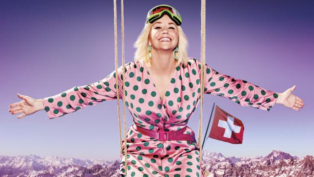 Beatrice Egli, auf einer Schaukel sitzend, im Sommerkleid, mit Skibrille und Bergen im Hintergrund