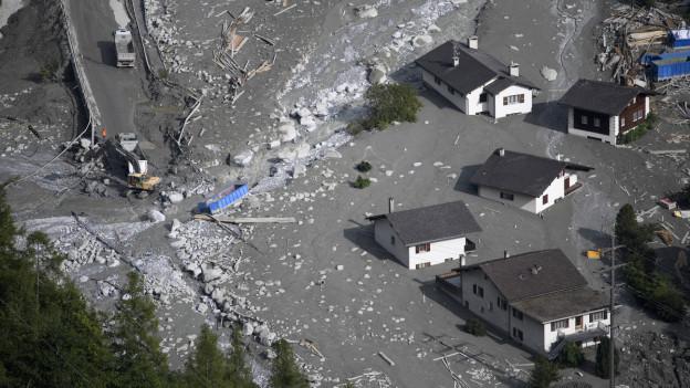 Luftaufnahme des Dorfes Bondo, das teilweise verschüttet ist von einer gewaltigen Schlammlawine
