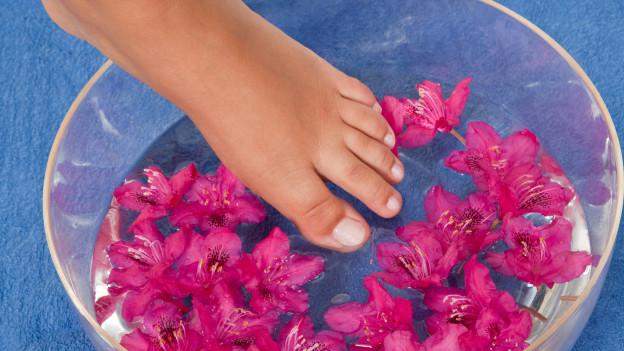 Füsse die in Fussbad mit Blumen tauchen