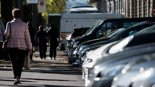 Strasse mit parkierten Auto am Rand.