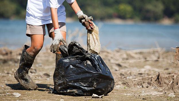 Mann mit Abfallsack reinigt ein Ufer.