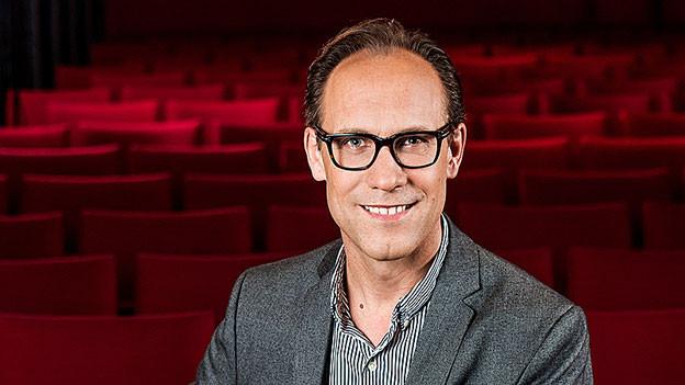 Porträt von Christian Zeugin in einem Theatersaal mit roten Sesseln.