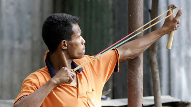 2006 greift dieser junge Mann bei einem Strassenkampf in Osttimor zum Stein als Waffe.
