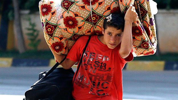 Alles, was er tragen kann: Ein Junge aus Syrien flüchtet mit seiner Familie über die türkische Grenze aus seiner Heimat.