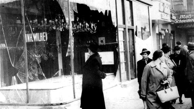 Passanten stehen vor einem jüdischen Geschäft, dessen Schaufenster während der Kristallnacht eingeschlagen wurden.