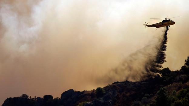 Ein Helikopter fliegt über einem brennenden Wald und schüttet Löschwassser aus.