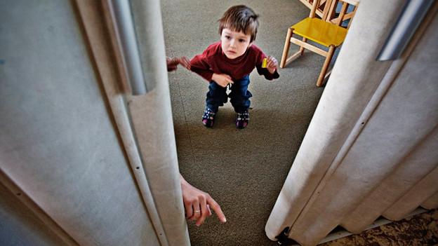 Ein kleiner Junge steht hinter einer Tür.