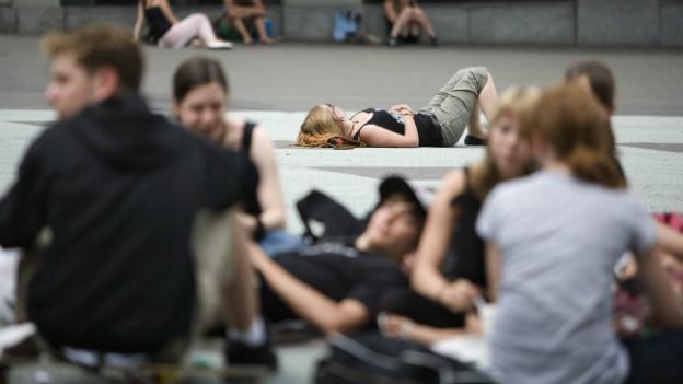 Jugendliche sitzen auf einem öffentlichen Platz