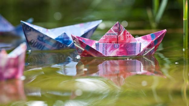Ein Papierschiffchen aus 20er-Noten auf dem Wasser
