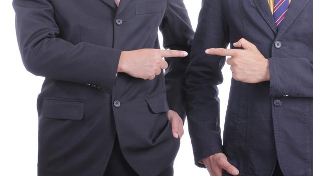 Zwei Männer im Anzug zeigen mit dem Finger auf den jeweils anderen.