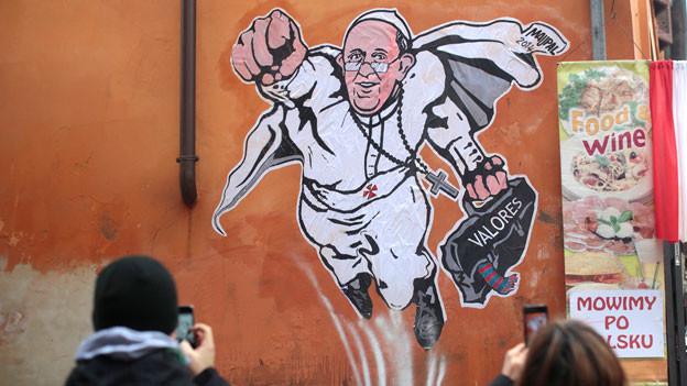Ein auf einer Hausmauer in Rom angebrachter Wandsticker zeigt Papst Franziskus als Superhelden.