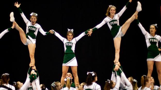 Cheerleader machen eine Menschen-Pyramide.