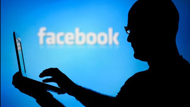 Das Bild zeigt einen Mann am Laptop vor dem Facebook-Logo.