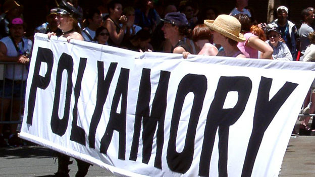 Demonstrantinnen halten grosses Banner «Polyamory».