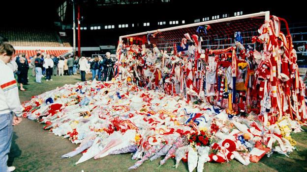 Man sieht ein Tor im Fussballstadion. Unzählige Blumen liegen vor dem Tor. Fussballschals hängen am Tor.