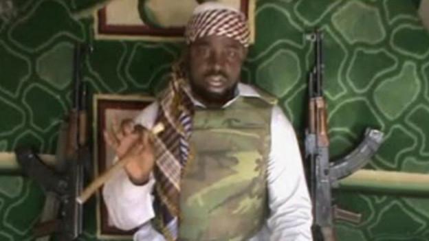 Videobild eines Mannes mit Turban und Camouflage-Schutzweste. Im Hintergrund zwei Gewehre.