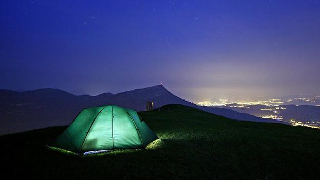 Ein beleuchtetes Zelt vor einem Sternenhimmel