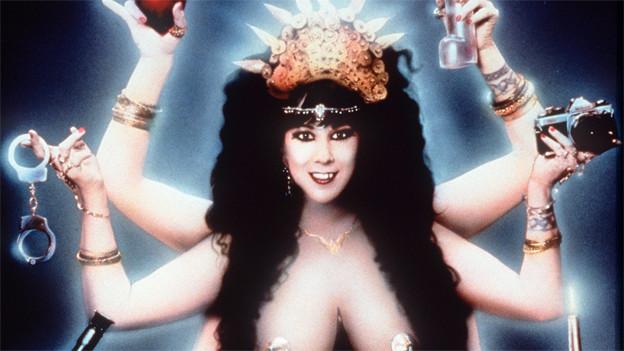 Ein nackte Frau mit sechs Armen hält eine Vielzahl von Gegensänden - u.a. Handschellen und einen Fotoapparat.