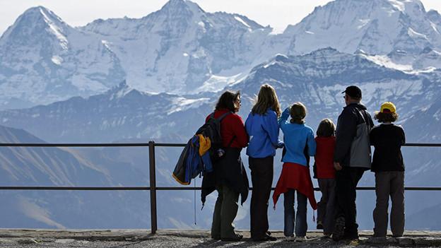 Eine Familie mit vier Kindern steht an einem Geländer und schaut auf eine Berglandschaft