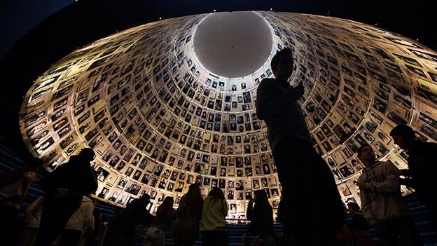 Das Innere eines runden Turmes. Die Wände sind vollständig mit Fotos bedeckt.