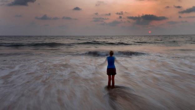 Eine Frau steht vor einem Meer.