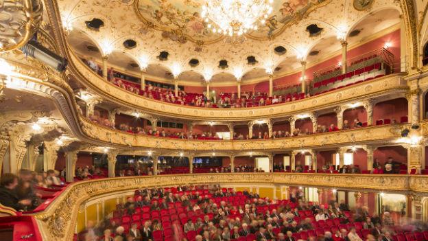 Blick auf das Zürcher Opernhaus. In den Reihen sind viele Besucher.