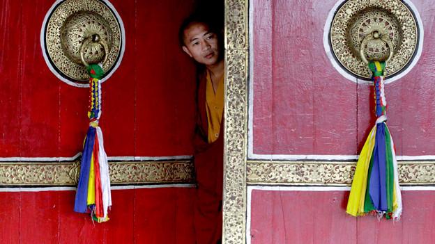 Tibetanischer Mönch streckt Kopf durch die Türe.