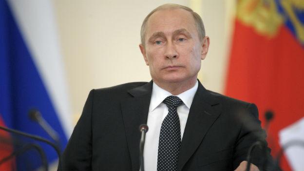 Vladimir Putin an einem Redner-Pult.