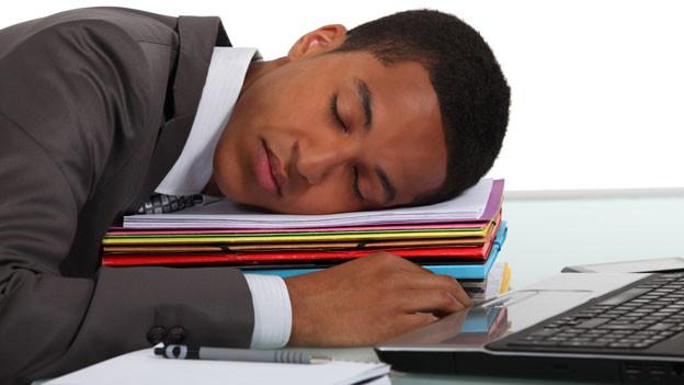 Ein Mann schläft auf einem Stapel Bücher.
