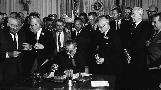 Schwarzweissfoto: An einem Tisch sitzt der Präsident und unterschreibt ein Dokument. Hinter ihm stehen etwa 40 Männer in Anzügen, direkt hinter dem Präsidenten ist Martin Luther King.