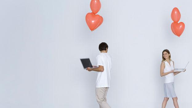 Ein Mann und eine Frau schauen sich an. Über ihren Köpfen herzförmige Ballone.