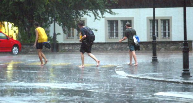 Drei Jungs rennen im Sommerregen.