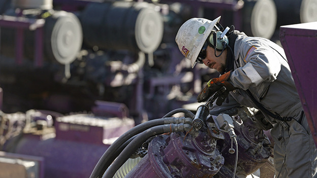 Ein Mann in Berufskleidung und Helm arbeitet an einer Maschine.