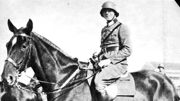 Mann in Militäruniform auf Pferd.