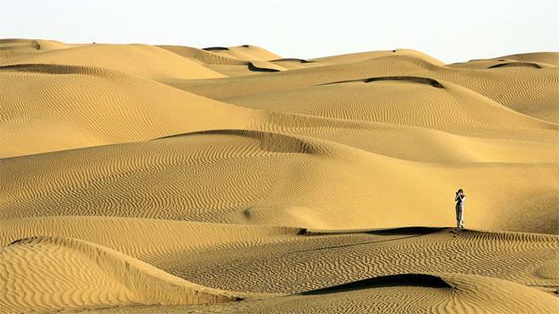 Eine Besucherin in der Taklimakan Wüste in China.