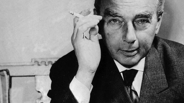 Porträt von Erich Kästner, der direkt in die Kamera schaut. In seiner rechten Hand eine Zigarette.