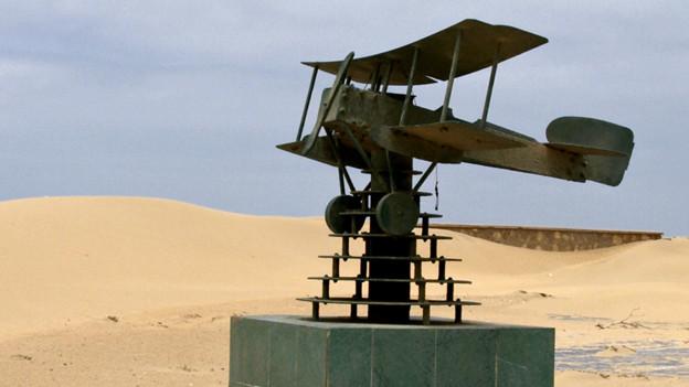 Ein Modellflugzeug steht vor einem Sandberg.