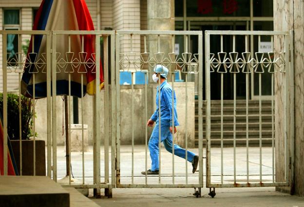 Blick durch einen Zaun: Ein Mann mit Mundschutz und blauer Spitalkleidung geht durchs Bild.
