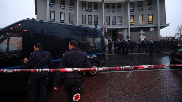 Polizisten vor einem Absperrband und einem Polizei-Kastenwagen.