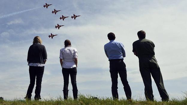 Menschen schauen Kampfjets zu, die in Formation vorbeifliegen.
