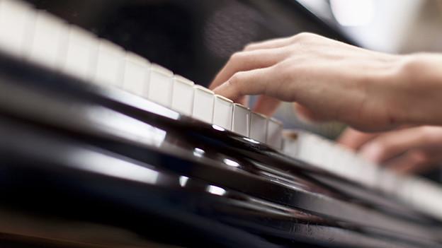 Hände auf einer Klaviertastatur