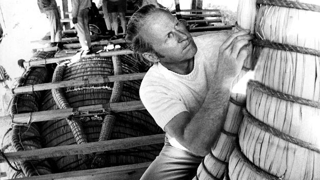 Thor Heyerdahl auf einem Schiff. Er scheint etwas reparieren zu wollen.